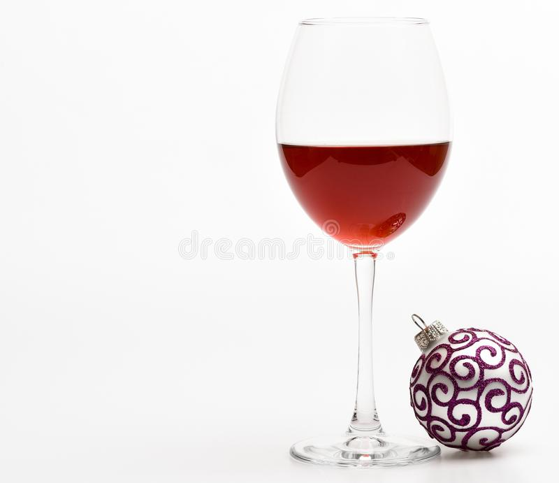 Winter celebration with alcohol drink. New year party concept. Wineglass with red liquid or wine and christmas ball royalty free stock photos