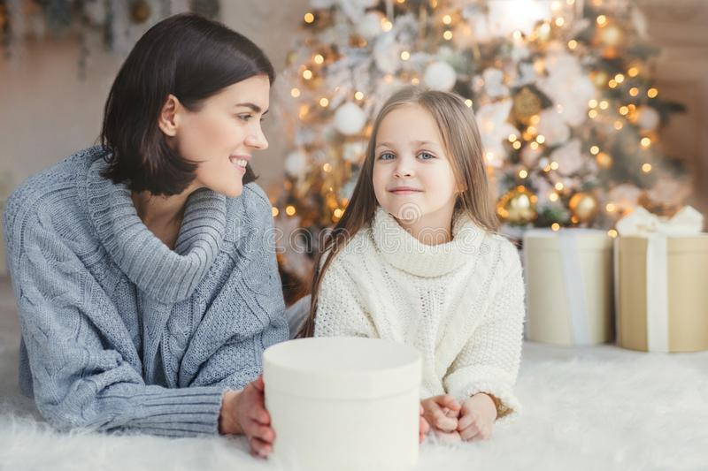 Winter and celebration concept. Pretty lovely blue eyed small female child in knitted white sweater and brunette female have good royalty free stock photography