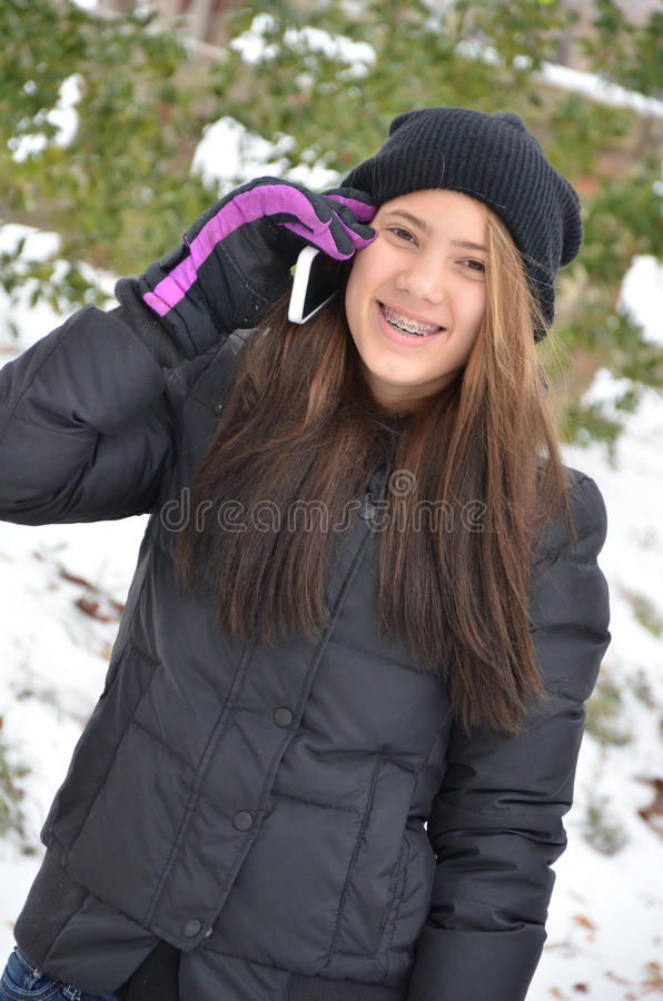 Winter Cell Phone. Teenage girl talking on her cell phone out in the snow stock image