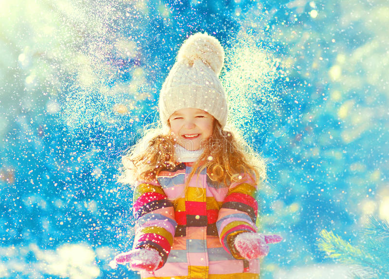 Winter cheerful little child playing throws up snow stock image