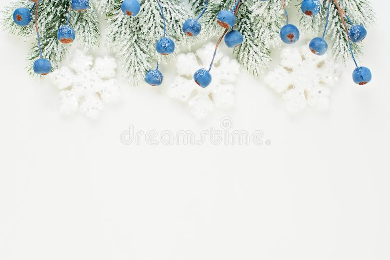 Winter Christmas card composition with blue berries, Xmas tree branch and Snowflakes isolated on white background. Winter decorations border stock images