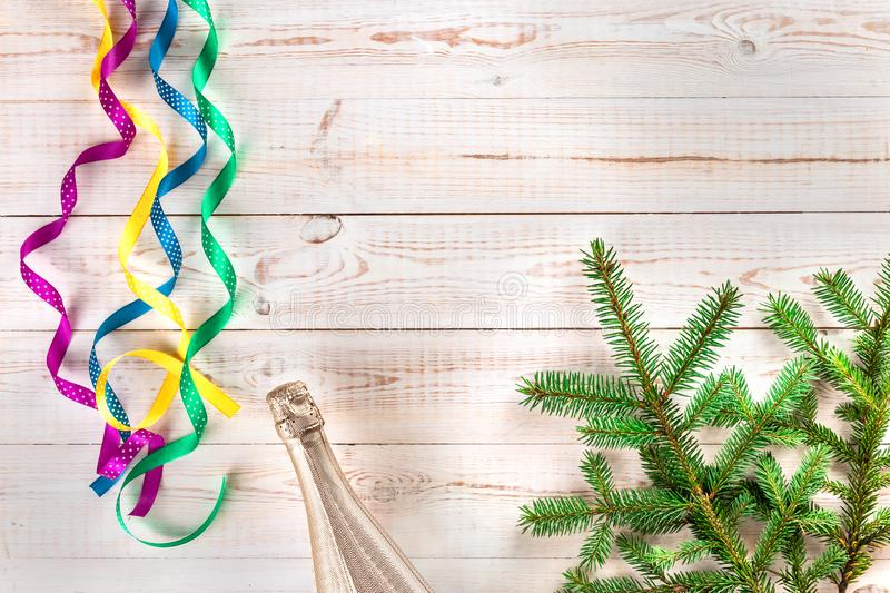 Winter Christmas composition with champagne bottle, pink, yellow, green, blue curly satin ribbons and spruce branch on white royalty free stock photos