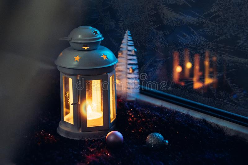 Winter Christmas Eve. Frosted window with Christmas decoration. Lantern with a lit candle near the window with frosty patterns on stock photography