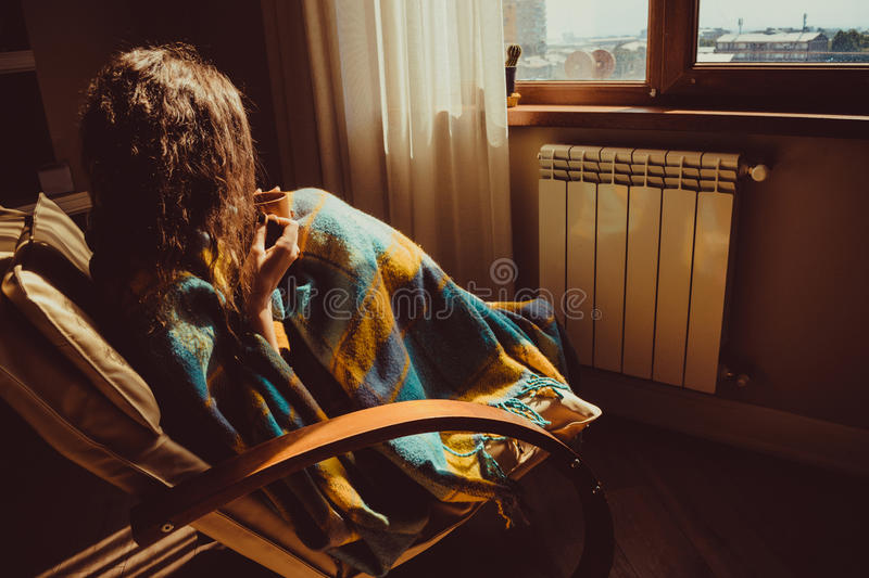 Winter and Christmas holidays concept. Young woman sitting in comfortable modern chair near radiator with mug of tea wrapped in wa stock photo