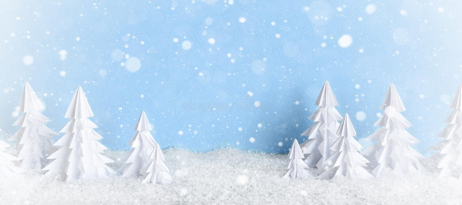 Winter Christmas minimalist background frosty baner with white paper trees on blue . royalty free stock photography