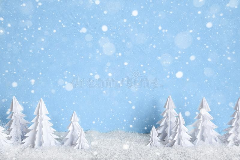 Winter Christmas minimalist background with white paper trees on blue drawing snowflakes. Winter Christmas minimalist background with white paper trees on blue stock photo