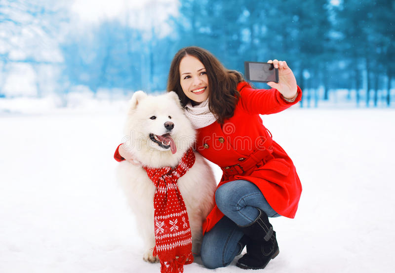 Winter, christmas, technology and people concept - woman and dog having fun takes selfie portrait on the smartphone. Winter, christmas, technology and people royalty free stock photography