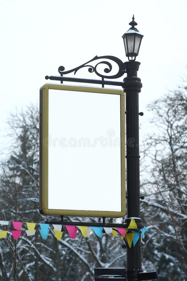 Winter city blank vertical billboard mockup on a classic lamp post royalty free stock photography