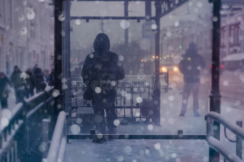 Winter city street and snow. Person standing alone. Blurred image of people royalty free stock images