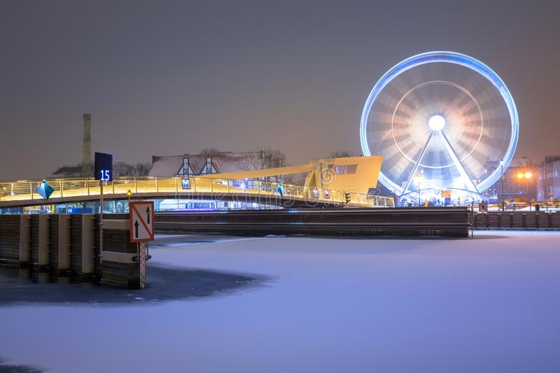 Winter cityscape of Gdansk at dusk with ferris wheel, Poland. Old beautiful port river town motlawa night landscape snow blue dawn polish light travel snowy stock image