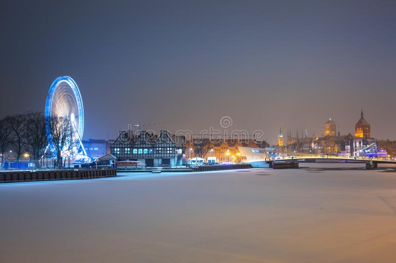 Winter cityscape of Gdansk at dusk with ferris wheel, Poland. Old beautiful port river town motlawa night landscape snow blue dawn polish light travel snowy royalty free stock images