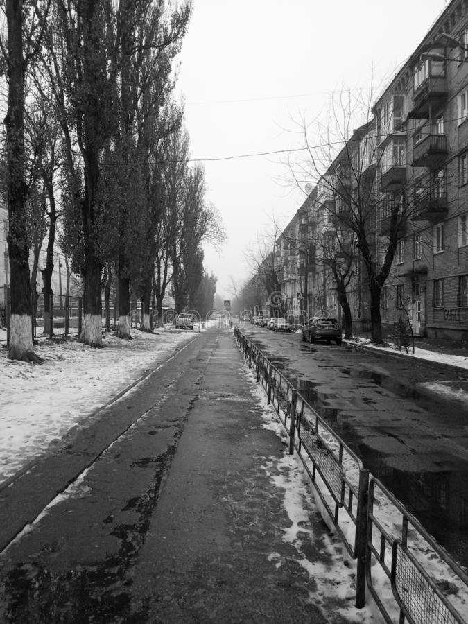 Winter cityscape. The street goes to the horizon. Black and white. Winter cityscape. The street goes to the horizon. The lines converge at one point. Black and stock photos