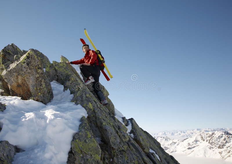 Winter climber. Male ski-climber climbing a rocky ridge; copy-space on the right. Italian alps stock images