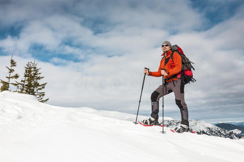 Winter climbing the mountain. A man in snowshoes is climbing to the top. Winter ascent. A mountaineer with a backpack and trekking sticks. Equipment for winter royalty free stock photos