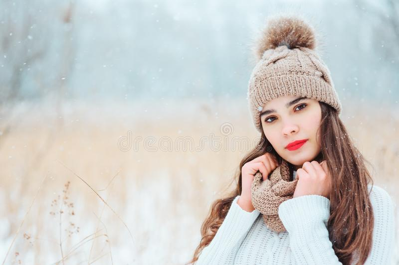 Winter close up portrait of beautiful smiling young woman in knitted hat and sweater walking outdoor under snowfall. Girl with red lipstick getting warm royalty free stock photos