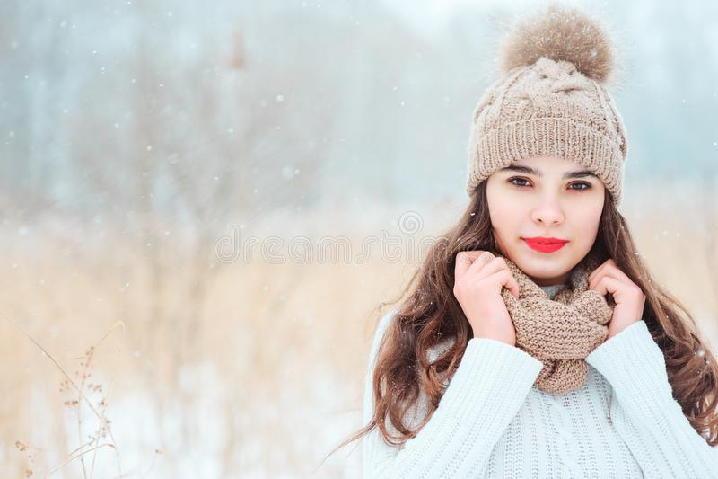 Winter close up portrait of beautiful young woman in knitted hat and sweater walking outdoor. Under smowfall. Girl with red lipstick getting warm stock photography