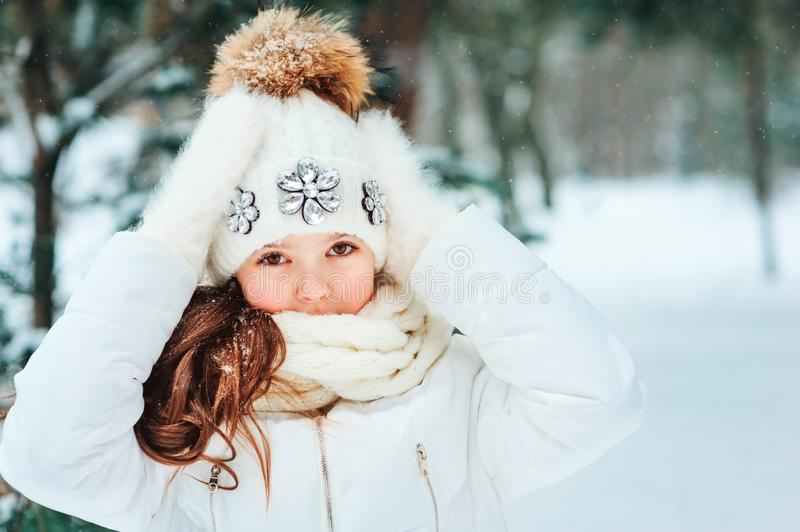 Winter close up portrait of cute dreamy child girl in white coat, hat and mittens. Playing outdoor in snowy winter forest. Traveling, vacation and active winter stock photography