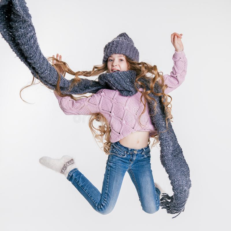Winter clothes. Little girl in grey hat and scarf jumping on the white background. Studio royalty free stock image