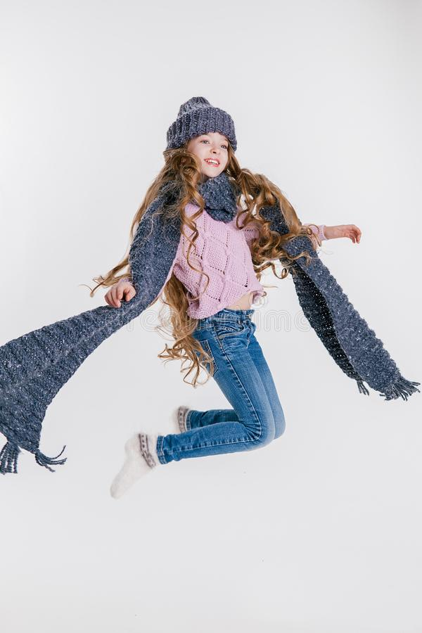 Winter clothes. Little girl in grey hat and scarf jumping on the white background. Studio stock image