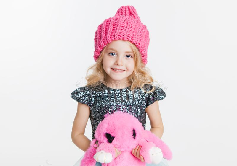 Winter clothes. Portrait of little curly girl in knitted pink winter hat isolated on white. Pink rabbit toy in her hands. Copy-space royalty free stock photos