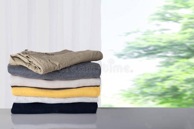 Winter clothes. Stack of colorful cozy warm sweaters and one jeans on table against blurred bright natural background. stock images