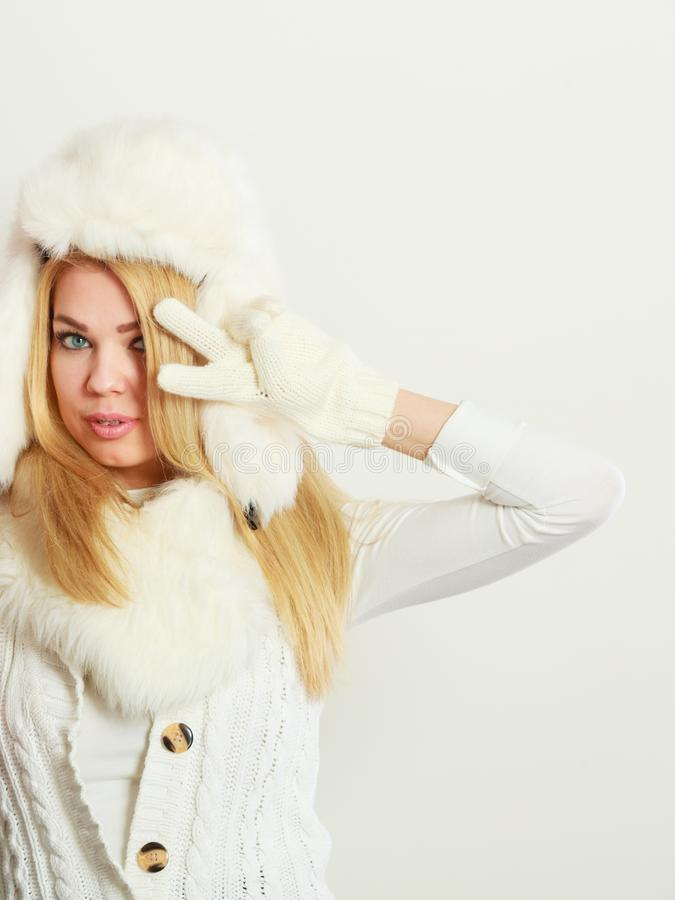 Blonde woman with fur cap. Winter clothing, people, fashion concept. Blonde woman with fur cap. Attractive lady has white outfit and gloves stock image