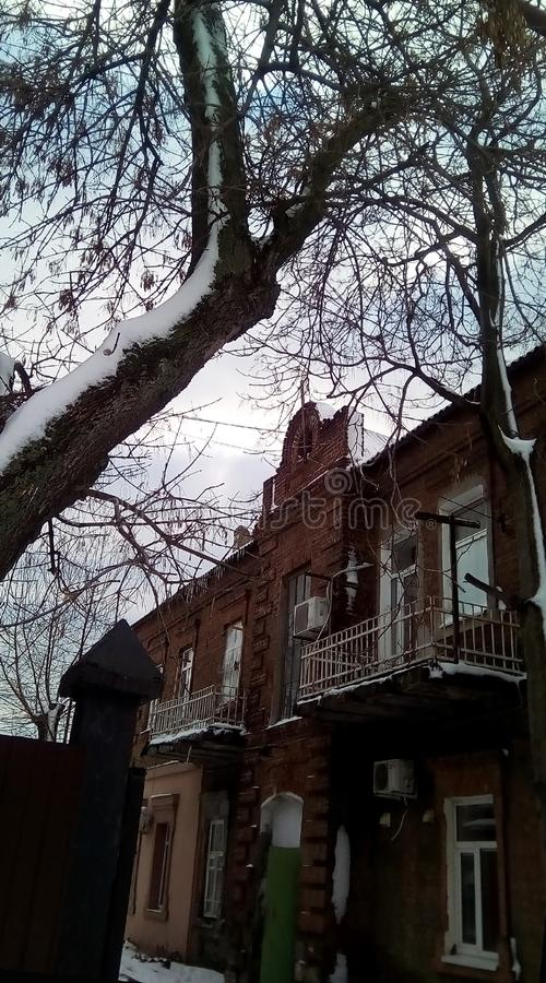 Winter cloudy day. An old snowy tree, part of the fence, courtyard, an old two-story building of dark red brick. stock photography