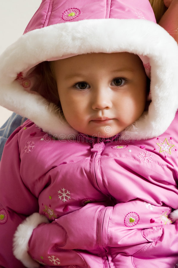 Winter coat. Portrait of face of an adorable caucasian blond baby girl toddler wearing pink winter coat with hood up stock image