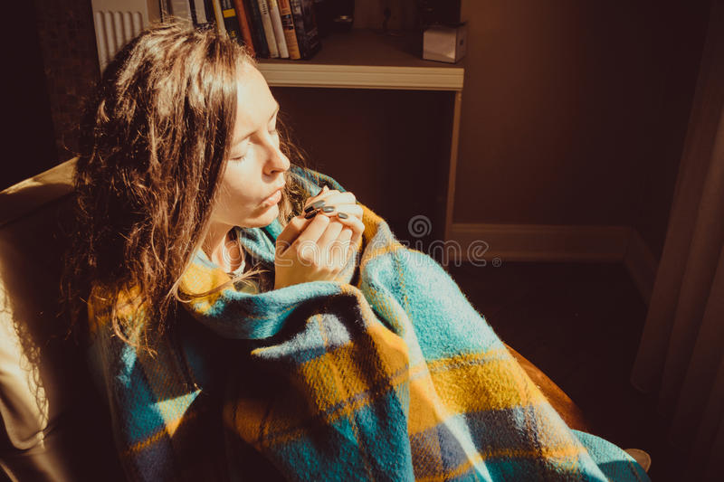 Winter cold concept. Young freezing woman in comfortable chair warming frozen hands wrapped in warm fluffy woollen plaid blanket. stock image