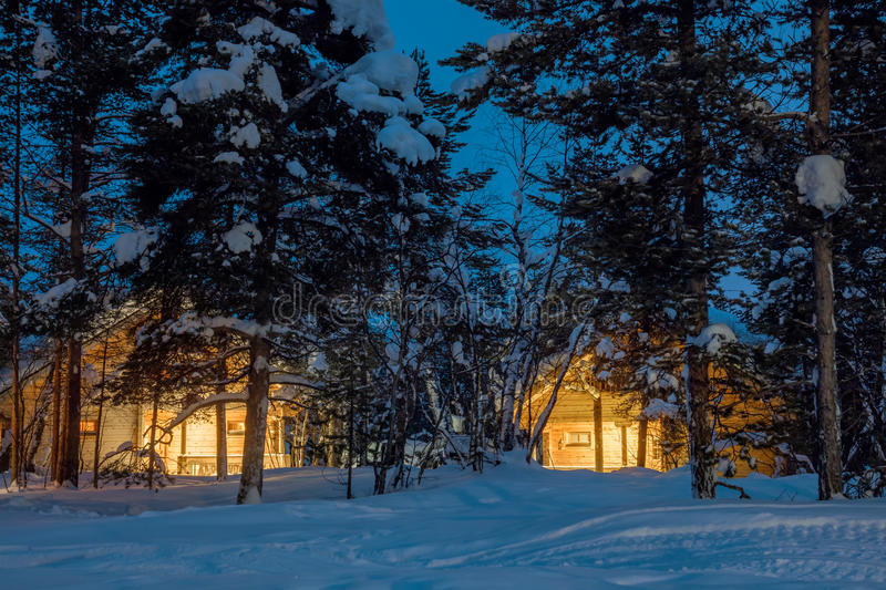Winter cold night, small wooden houses with warm light. A lot of snow, quiet winter landscape stock photo