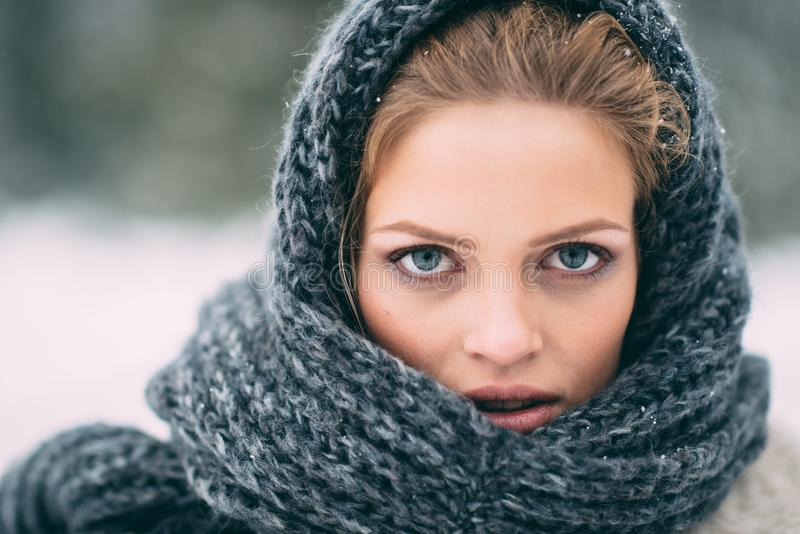 Young and blond girl wearing blue scarf in winter stock image
