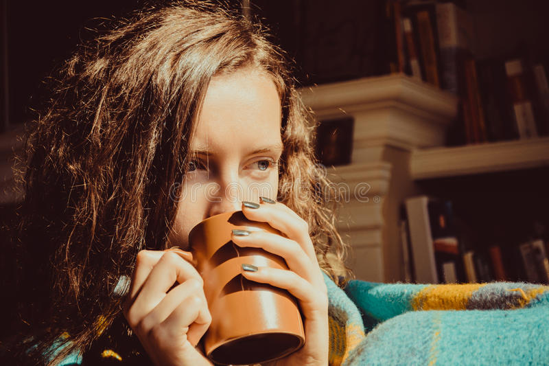 Winter cold sickness concept. Young freezing pensive woman with mug tea wrapped in warm plaid blanket. Natural light. Warm atmosph stock photos