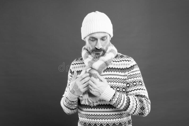 Winter collection. Warmth and comfort. Cold winter conditions. Handsome bearded man wearing hat and scarf red background royalty free stock image