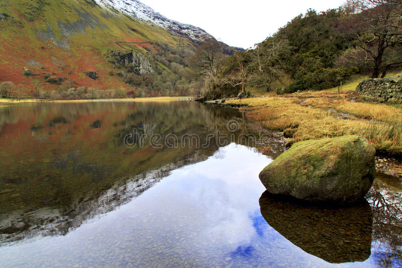 The winter colours of ILlydd foothills reflected in the peaceful waters of Llyn Gwynant. Snowdonia, Wales stock photos