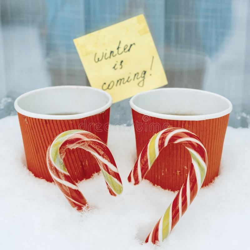 Winter is coming, snowy background, two christmas candi canes in the shape of a heart, two cup of coffee.  royalty free stock photos