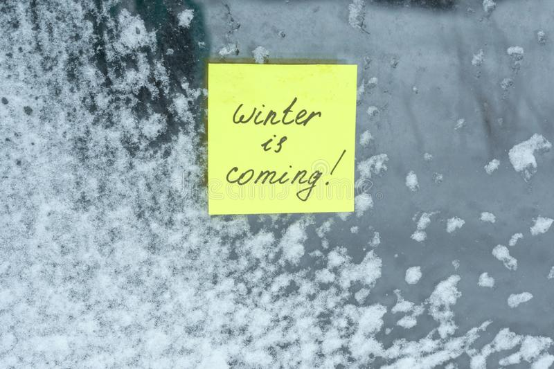 Winter is coming, texture background snow-covered window with a sticker.  stock photos
