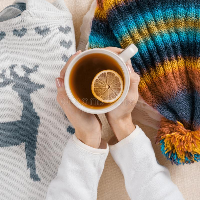 Winter is coming, womens hands are holding cup of hot tea with lemon, background is warm seasonal clothes, close-up view from. Winter is coming, women hands are stock image