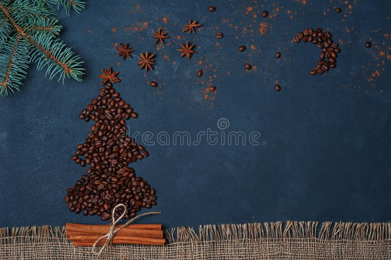 Winter composition Christmas tree made by coffee beans with night sky by anise star and chocolate. Greeting card New Year. royalty free stock photography