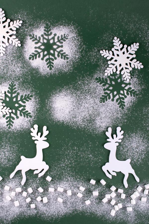 Winter composition with deers and snowflakes. On green background. Christmas card. royalty free stock image