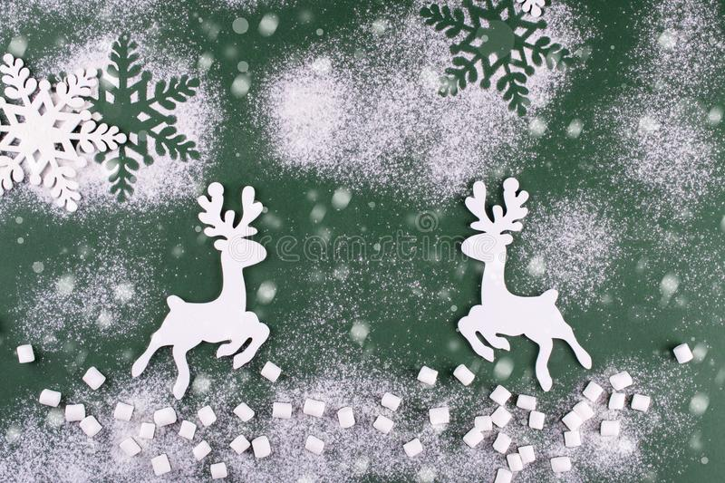 Winter composition with deers and snowflakes. On green background. Christmas card. stock photo