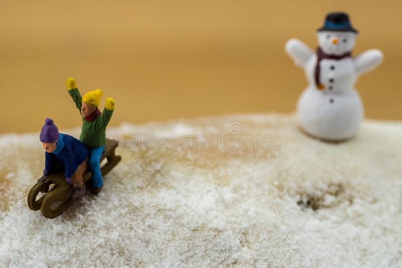 Winter concept children sliding down snowy mountain stock photography