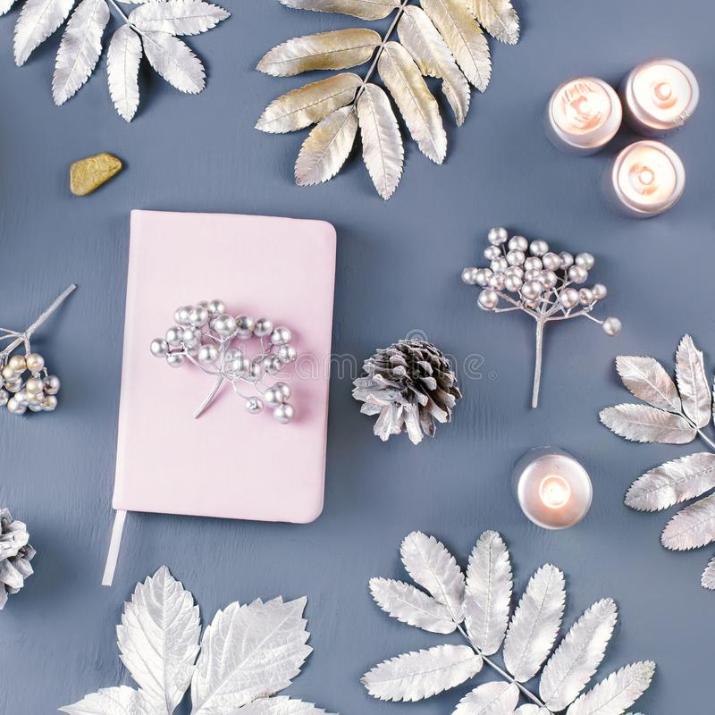 Winter concept flat lay with coffee drink, notebook, candles and silver leaves, copy space. Top view royalty free stock photography