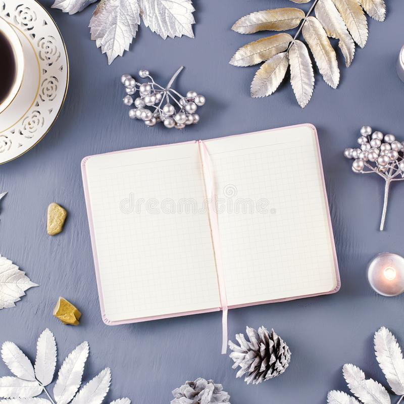 Winter concept flat lay with coffee drink, open blank notebook, candles and silver leaves, copy space stock images