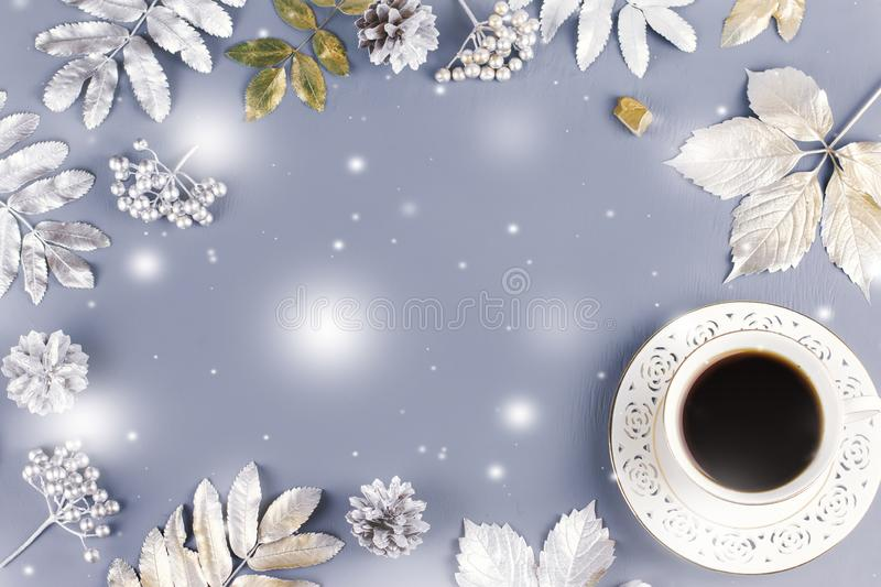 Winter concept flat lay with coffee drink and silver leaves, copy space. Christmas frame background. royalty free stock photo