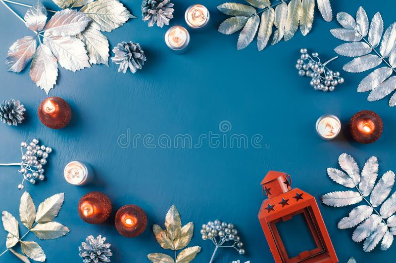 Winter concept flat lay with golden and silver leaves and red candles. Christmas frame background. Winter concept flat lay with golden and silver leaves and red royalty free stock image