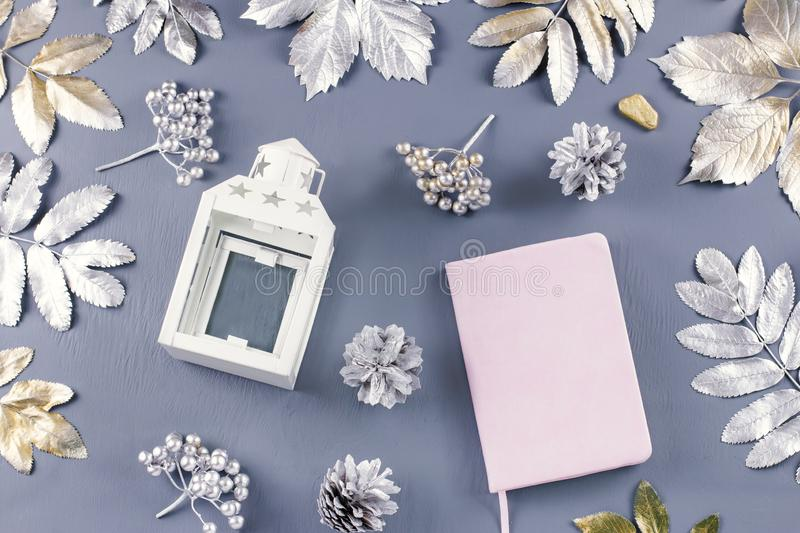 Winter concept flat lay with lantern, note book, candles and silver leaves. royalty free stock photography