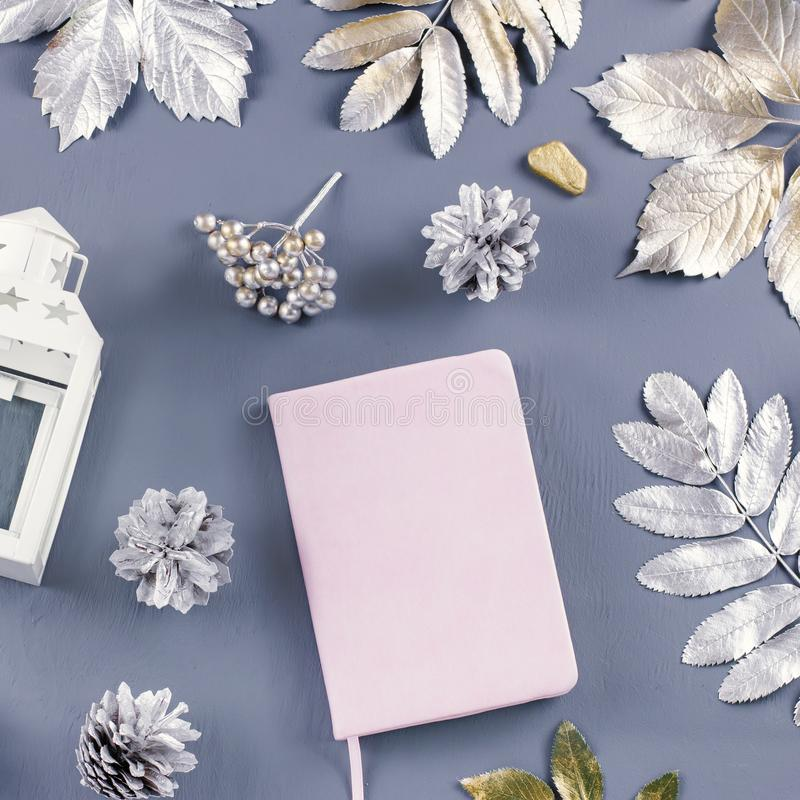 Winter concept flat lay with lantern, note book, candles and silver leaves. stock photos