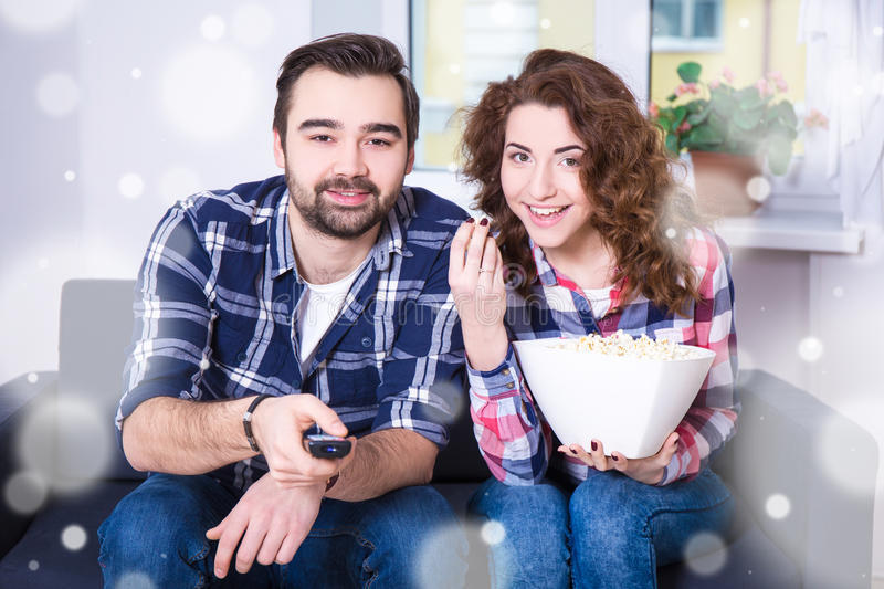 Winter concept - happy young couple watching tv or movie at home royalty free stock photos