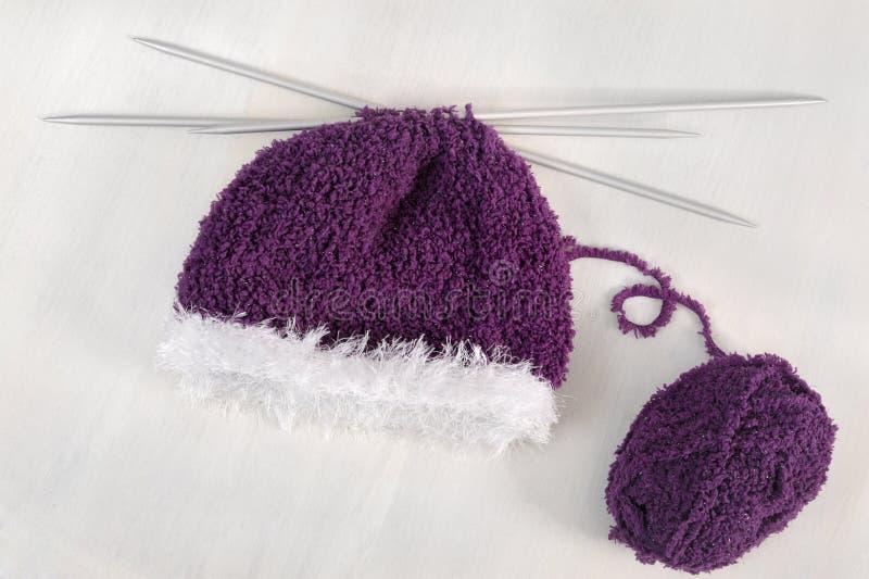 Winter concept: purple bonnet & knitting needles. Winter concept : purple bonnet with knitting needles and ball stock photo