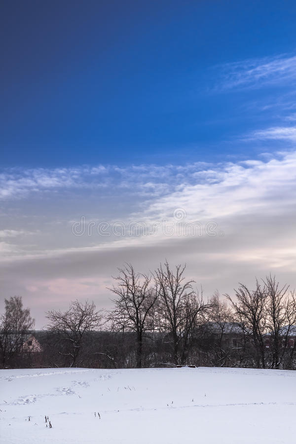 Winter countryside landscape at snow field and blue sky on horizon with beautiful cloudscape royalty free stock image
